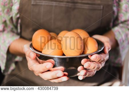 Female Hands Hold A Silver Bowl Of Chicken Eggs
