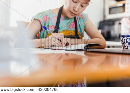 Baker Woman In Apron Work At Table Write Down Recipe Indoor