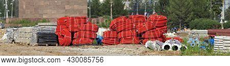Flexible Corrugated Pipes For Cable Laying Are Rolled Up. Metal Supports, Pipes, Curbstone And Other