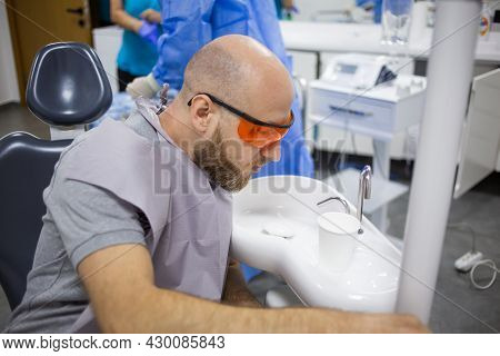 Caucasian Male Is Rinsing His Mouth During A Wisdom Tooth Extraction Surgery In A Dental Hospital.