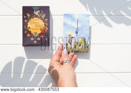 Deck Of Green Witch Tarot Cards And Hand Holding Ace Of Athames Card On White Wooden Surface With Sh
