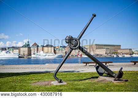 Old anchor on waterfront in Stockholm , Sweden. Shallow DOF, focus on the anchor