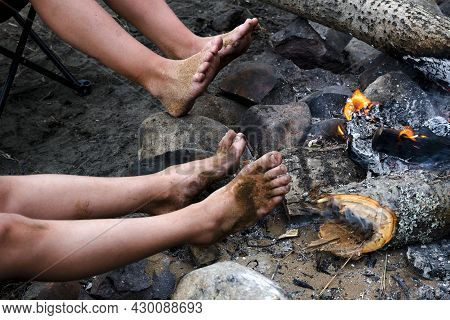 Children Warm Their Dirty Feet After Swimming On Campfire At Campsite. Barefoot Children's Legs Warm