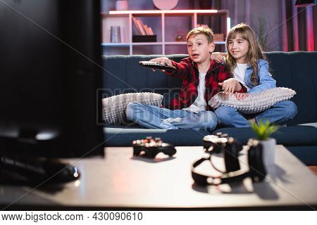 Happy Caucasian Kids Using Remote Control For Choosing Cartoon On Tv While Sitting On Comfy Couch. B
