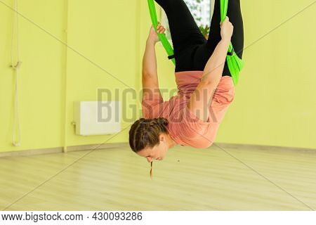 A Young Girl Practices Yoga On A Hammock In The Hall. The Girl Performs Asanas In Limbo.