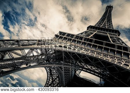 Eiffel Tower with blue sky and cloud background. Low angle view looking up. Built by engineer Gustave Eiffel, and opened in 1889. Champ de Mars, Paris, France.