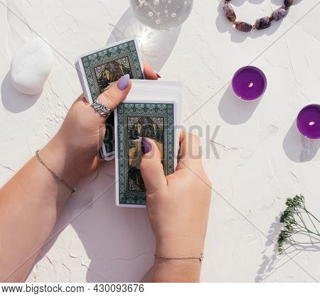 Hands With Purple Nails And Rings Hold Deck Of Tarot Cards On White Surface With Crystal Ball, Candl