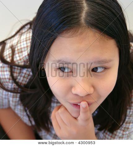 Schoolgirl With Finger To Lips