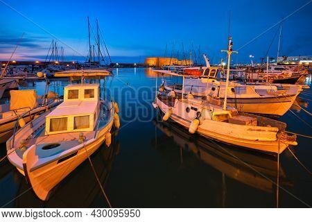 Venetian Fort Venetian fortress of Koules Castello a Mare castle in Heraklion and moored Greek fishing boats in port, Crete Island, Greece in twilight
