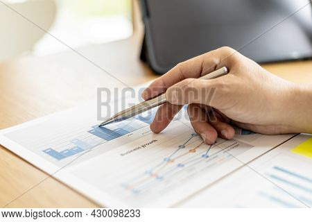 The Financial Officer Uses A Pen To Point At The Numbers On The Financial Documents To Verify The Co