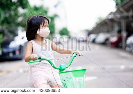 Girl Wearing Cloth Mask Is Riding Green Bike Playing Outside While Coronavirus (covid-19) Is Spreadi