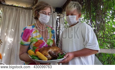 Moscow, Russia-july 25, 2021. A Grandmother Passes A Festive Thanksgiving Dish To Her Teenage Grands
