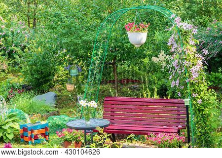 Part Of The Garden Garden With An Arch For Tall Vines, A Garden Wooden Bench With A Glass Table, A P