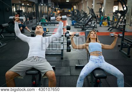 Fit couple doing exercise with dumbbells in gym