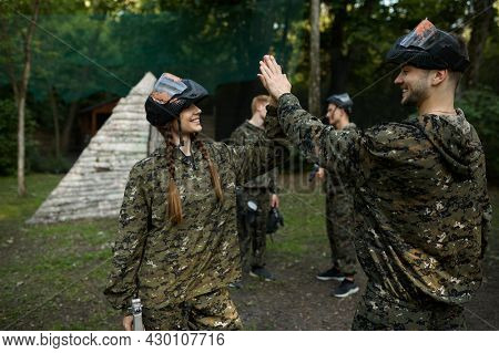 Team in camouflages and masks playing paintball