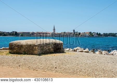 An Old World War Two Bunker On The Coast Of Istria In Croatia With The Historic Medieval Town Of Por
