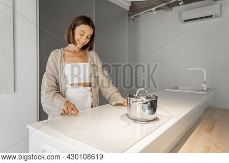 Young Stylish Woman Cooking On Induction Hob At Modern Kitchen. Concept Of Smart Technologies Of Kit
