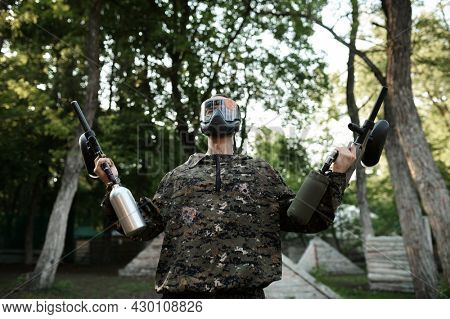 Paintball warrior poses on playground in forest