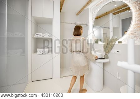 Lifestyle Portrait Of A Woman At Modern And Bright Bathroom Interior. Woman Feeling Well Being At Co