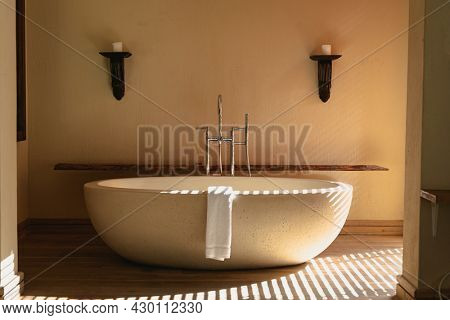 Interior of sunny, modern luxury bathroom with beautiful designer bath. modern architecture and domestic interior design.