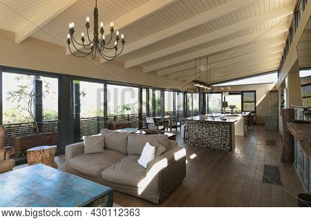 Interior of open plan kitchen diner and living room of comfortable home, with windows to terrace. modern architecture and domestic interior design.