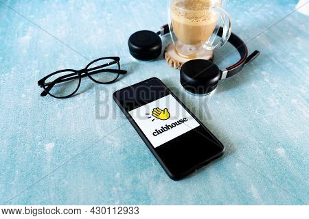 Flatlay Shot Of Mobile Phone With The Clubhouse Audio Only Social Media App With Spectacles Headphon