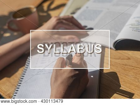 Syllabus Word Over Photo With Hand Closeup Writing In Notebook.