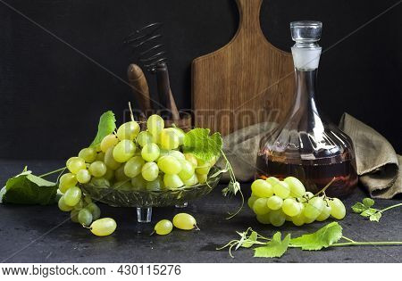 Fresh Ripe Grapes In A Fruit Bowl And Decanter With Grape Juice. Kitchen Utensils On Background