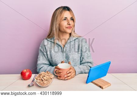 Young caucasian woman having breakfast looking at the tablet sitting on the tablet smiling looking to the side and staring away thinking.