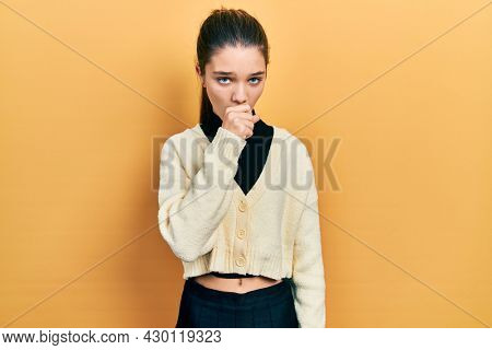 Young brunette girl wearing casual yellow jacket feeling unwell and coughing as symptom for cold or bronchitis. health care concept.