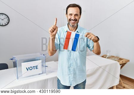 Middle age man with beard at political campaign election holding nederlands flag smiling with an idea or question pointing finger with happy face, number one