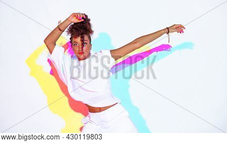 Dancing Mixed Race Girl In Colourful Light On White Studio Background. Female Dancer Performer With
