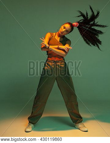 Confident Young Mixed Race Girl With Afro Hairs Tail Standing With Waving Hair In Studio Spotlight