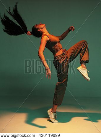 Dancing Athletic Mixed Race Girl Performing Expressive Fiery Hip Hop Or Ethnic Modern Dance In Colou