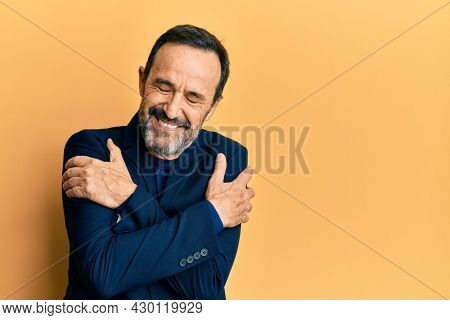 Middle age hispanic man wearing business clothes hugging oneself happy and positive, smiling confident. self love and self care