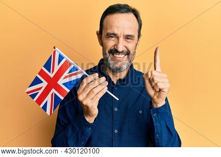 Middle age hispanic man holding united kingdom flag smiling with an idea or question pointing finger with happy face, number one