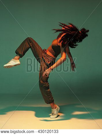 Dancing Mixed Race Girl With Afro Hairs In Colourful Studio Light. Female Dancer Performing Expressi