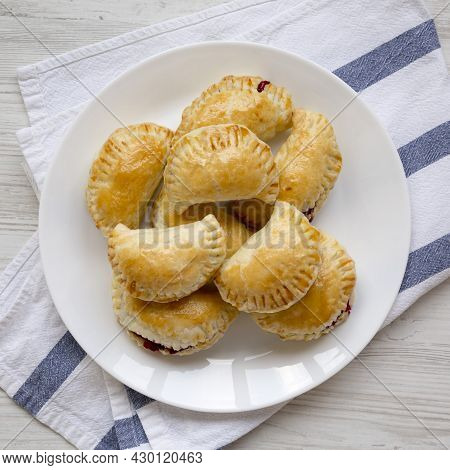 Homemade Cherry Hand Pies On A Plate On A White Wooden Table, Overhead View. Top View, From Above, F