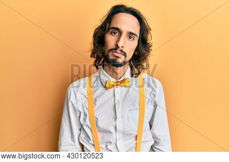 Young hispanic man wearing hipster elegant look relaxed with serious expression on face. simple and natural looking at the camera.