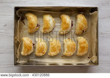 Homemade Cherry Hand Pies In A Baking Pan, Top View. Flat Lay, Overhead, From Above.