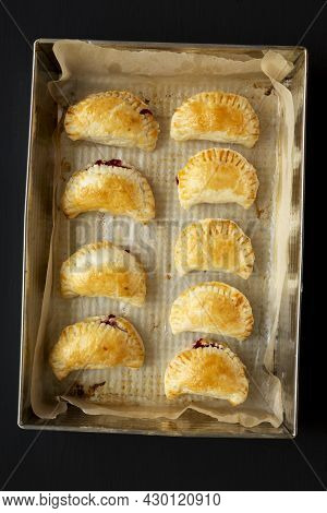 Homemade Cherry Hand Pies In A Baking Pan On A Black Background, Top View. Flat Lay, Overhead, From