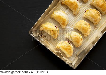 Homemade Cherry Hand Pies In A Baking Pan On A Black Background, Top View. Space For Text.