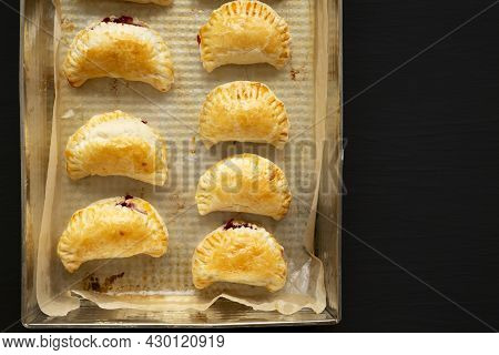 Homemade Cherry Hand Pies In A Baking Pan On A Black Surface, Top View. Copy Space.