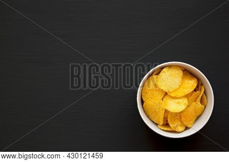 Ruffled Cheese Potato Chips In A Bowl On A Black Background, Top View. Flat Lay, Overhead, From Abov
