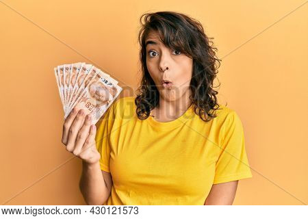 Young hispanic woman holding 50 turkish lira banknotes scared and amazed with open mouth for surprise, disbelief face