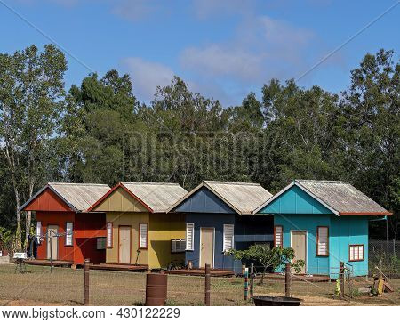 A Row Of Colorful Tiny Houses In A Rural Area, Each With Their Own Front Door And Small Porch Deck