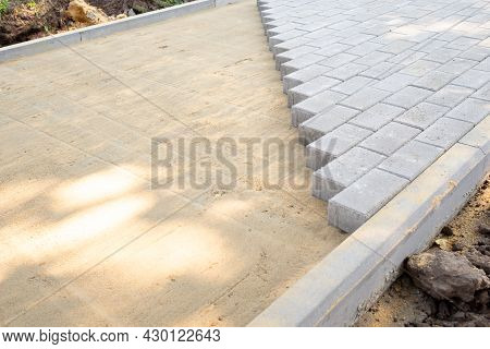 Paving Slabs Or Paving Stones Are Laid Out On The Sand Between The Curbstone. The Process Of Buildin