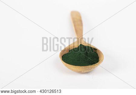 Organic Spirulina Algae Powder In Wooden Spoon On White Background. Close-up
