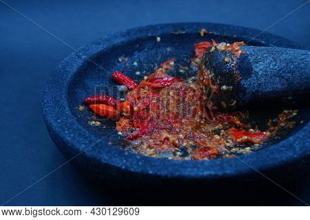 Red Chili Sauce On A Stone Mortar And Pestle. Dark Background, Focus Selected.