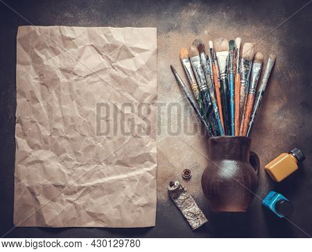 Paint brush and art painter tool on abstract background texture. Paintbrush for painting and piece of paper as artistic paint still life. Abstract art concept